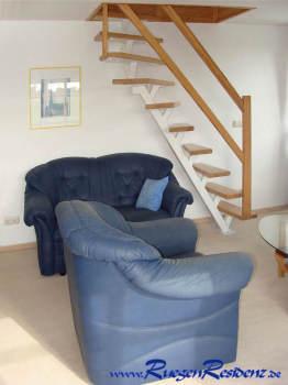 Aus dem Wohnzimmer führt die Treppe im Hintergrund hinauf ins Dachgeschoß