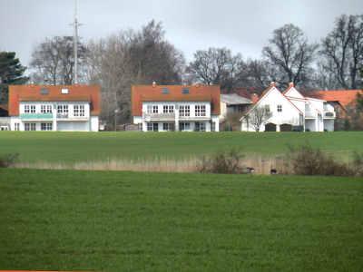Blick über die Felder auf die Ferienwohnungen Zudar in grüner Ortsrandlage