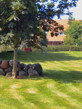 Blick durch den Garten auf die Terrassenseite des Gutshauses