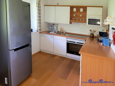 Moderne Einbauküche mit Herd, Spülmaschine, Mikrowelle, Kaffeemaschine