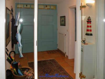 Durch die große rustikale Haustür geht es in den modernen gläsernen Flur