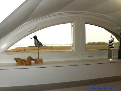 Blick aus dem Schlafzimmerfenster über Wiesen zum Wasser